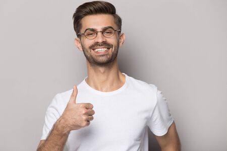 Happy smiling millennial guy in eyewear showing thumbs up gesture, isolated on grey studio background. Satisfied male client recommending whitening teeth or ophthalmology clinic services portrait. 版權商用圖片