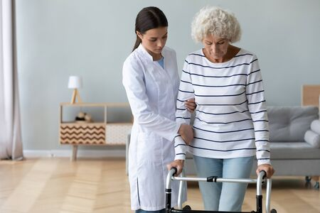 Serious doctor teaching disabled older woman to use walker at home, caregiver holding mature female patient hand, supporting, helping to walk, rehabilitation and recovery after injury, orthopedic Stock Photo