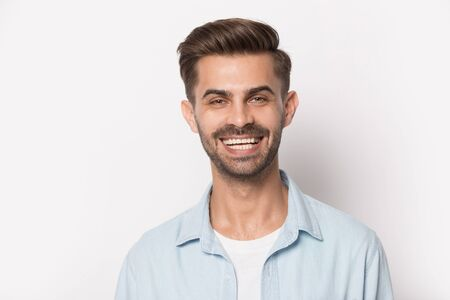 Head shot close up young excited happy man portrait. Smiling millennial guy looking at camera, isolated on white studio background. Dental clinic healthy satisfied customer on empty blank copy space. Banco de Imagens