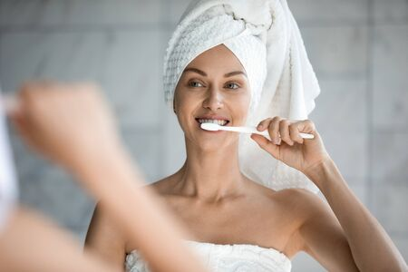 Head shot close up beautiful woman with healthy perfect smile brushing teeth, looking in mirror, attractive young female wearing white bath towel on head standing in bathroom, oral hygiene