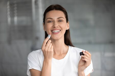 Head shot portrait happy beautiful woman with healthy toothy smile applying pink lipstick, looking at camera, excited young female with perfect healthy skin doing everyday makeup, morning routine