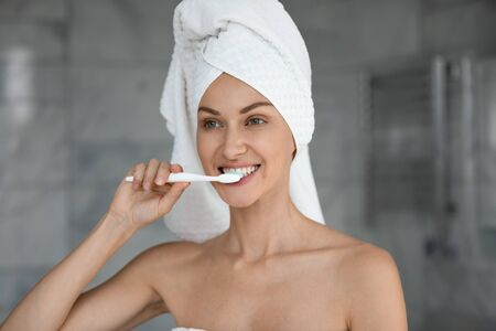 Head shot beautiful woman with white bath towel on head brushing teeth close up, morning routine, oral hygiene concept, pretty young female with healthy toothy smile standing in bathroom after shower Banco de Imagens