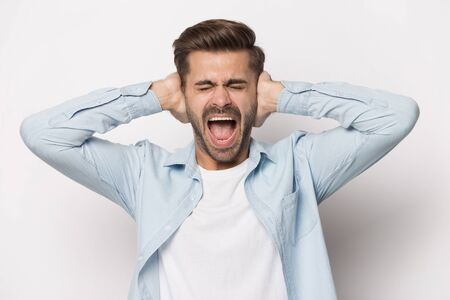 Annoyed young man covering ears with hands, screaming, shouting, refusing to listen, isolated on white studio background. Stressful guy avoiding loud noisy sounds, suffering from headache or migraine. Banco de Imagens