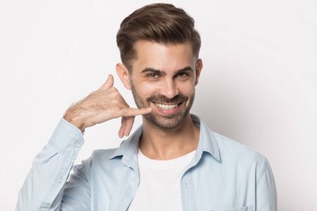 Happy smiling young guy showing call me back body language gesture head shot close up portrait. Isolated on white studio background joyful man, imitating cell phone call, mobile communication concept.