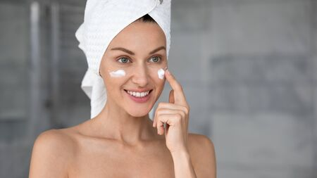 Head shot close up beautiful woman with perfect smooth skin applying cream on cheeks, pretty young female with white bath towel on head and healthy smile touching face, using moisturizer Banco de Imagens - 138135999
