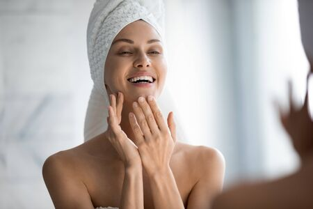 Head shot happy beautiful woman wearing white bath towel on head looking in mirror in bathroom, pretty young female with toothy smile satisfied by healthy smooth perfect skin, touching face close up
