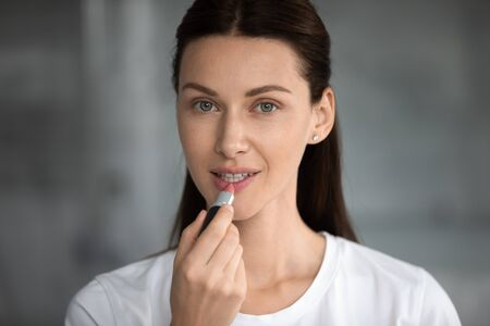 Head shot portrait close up beautiful woman applying pink lipstick on lips, looking at camera, attractive young female with perfect healthy skin doing everyday makeup, morning routine