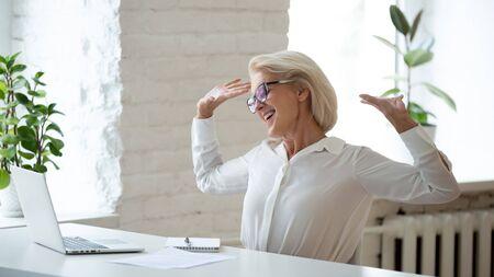 Bastante empresaria de mediana edad relajante sentado en una silla en el lugar de trabajo durante las vacaciones, comienza la jornada laboral se siente satisfecha. Sonriente mujer madura jefe u oficinista estirando los brazos disfrutar de la jornada laboral termina Foto de archivo