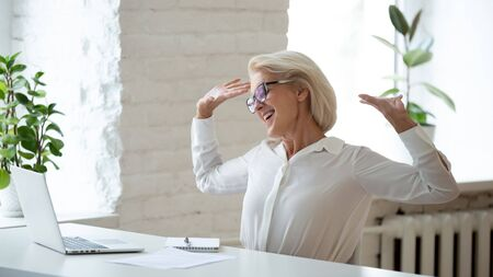 Pretty middle-aged businesswoman relaxing seated on chair at workplace during break, starts workday feels satisfied. Smiling mature female boss or office worker stretching arms enjoy working day ends