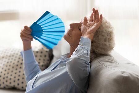 Donna anziana esausta che si sente male, tocca la fronte con la mano, soffre di calore, agita il ventaglio di carta blu da vicino, si siede sul divano, donna matura che si raffredda nel caldo clima estivo, alta temperatura Archivio Fotografico