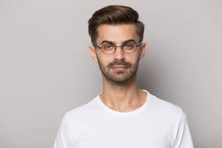 Isolated on grey studio background young guy wearing eyeglasses head shot close up portrait. Serious millennial man looking at camera, vision correction concept or optics store lenses advertisement. Banco de Imagens