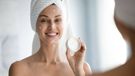 Head shot portrait beautiful woman with healthy perfect smooth skin applying face cream, pretty young female with bath towel on head showing cosmetic product, looking in mirror in bathroom