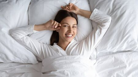 Head shot portrait top view smiling beautiful woman lying in comfortable bed, looking at camera, young female wearing pajamas resting on soft pillows in bedroom, enjoying morning after awakening Banco de Imagens - 138136025