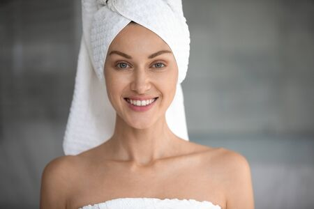 Head shot portrait close up beautiful woman with white bath towel on head and naked shoulders looking at camera, pretty young female with healthy toothy smile and smooth perfect skin in bathroom