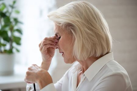 Close up of middle-aged blond woman taking off glasses reduces eye strain closed eyes touch rubs nose bridge, elderly businesswoman at workplace feels unwell sleepy insomnia, visual impairment concept Standard-Bild