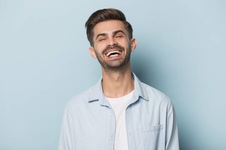 Happy overjoyed millennial man head shot studio portrait. Young guy laughing on funny joke, having fun, isolated on blue background. Satisfied cheerful smiling dental clinic client posing for photo.