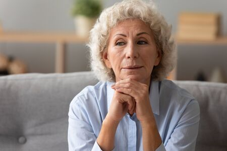 Head shot close up peaceful older woman dreaming thinking about good future alone, sitting on couch at home alone, dreamy mature female with grey curly hair looking in distance, feeling satisfied Banco de Imagens - 138136055