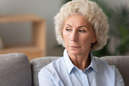 Disparo a la cabeza de cerca una mujer mayor perdida en pensamientos, mirando hacia un lado, sentada en el sofá en casa sola, mujer madura pensativa pensando en el problema, la nostalgia y la melancolía, sintiéndose sola Foto de archivo