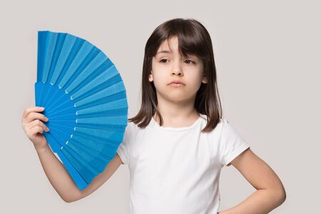 Upset sweating six years old girl waving fan. Overheated unhappy little preschool cutie suffering from heat stroke, high temperature inside or hot summer weather, isolated on beige studio background.