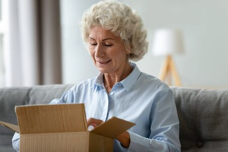 Smiling older woman unpacking cardboard box close up, sitting on couch at home, satisfied mature female, curious customer received parcel online store order, gift from relatives, delivery service
