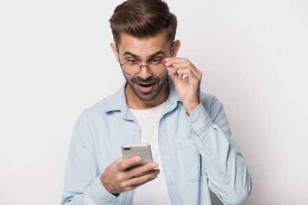 Young shocked man holding eyeglasses cant believe his eyes, looking at smartphone screen, reading email with unbelievable news, huge discount coupon, sale announcement, isolated on white background. Banco de Imagens - 138136065