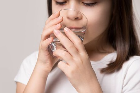 Close up cropped head shot little healthy happy preschool girl holding and drinking glass of fresh pure water, isolated on beige studio background. Dehydration prevention, daily healthy habit concept. Banco de Imagens - 138136067