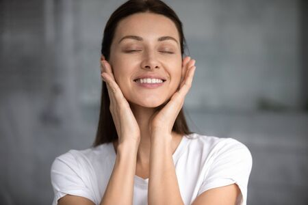 Head shot satisfied smiling woman with perfect smooth and healthy toothy smile skin touching cheeks, beautiful young female with closed eyes making face massage close up, natural beauty concept