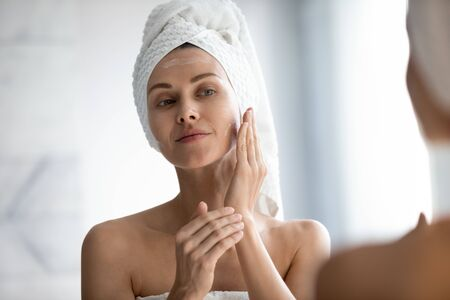 Head shot close up beautiful peaceful woman applying moisturizer on skin, looking in mirror, standing in bathroom, pretty young female with white bath towel on head using cream, touching face Banco de Imagens