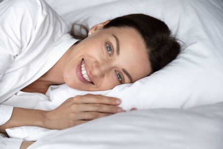 Head shot portrait beautiful woman wearing white pajamas resting on soft pillow in comfortable bed, happy young female with healthy smile looking at camera, relaxing in bedroom, enjoying morning