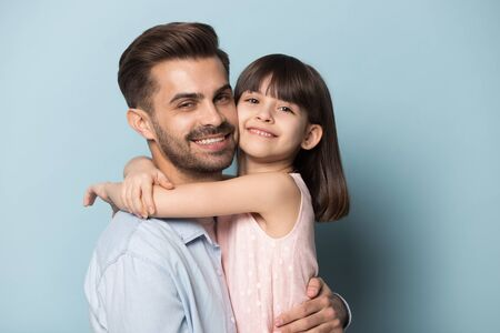 Head shot portrait adorable smiling six years old little preschool girl embracing happy young father or elder brother, posing for photo, looking at camera, isolated on blue studio background. Imagens