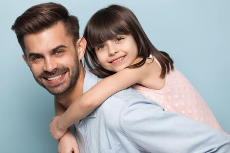 Headshot close up portrait happy young single dad holding little funny preschool smiling daughter on back, looking at camera, isolated on blue studio background, warm relations, Fathers day concept. Banco de Imagens - 138136082