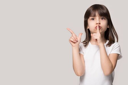 Adorable preschool brown-haired girl showing hush secret sign, pointing at copy space for advertising text, big sale announce. Little cutie holding finger on lips, isolated on grey studio background.