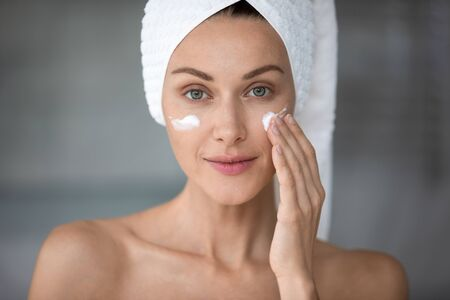 Head shot portrait close up beautiful woman with healthy perfect smooth skin applying moisturizing cream on cheekbones, touching cheek, pretty young female with bath towel on head looking at camera Banco de Imagens - 138136087