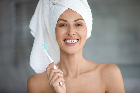 Head shot portrait close up beautiful woman with healthy toothy smile holding toothbrush, pretty young female wearing white bath towel on head looking at camera, standing in bathroom, oral hygiene Banco de Imagens - 138136088
