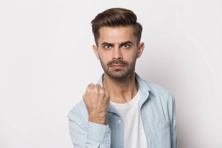 Isolated on white studio background angry young guy squeezing hand into fist, showing power, trying to threaten or giving warning. Head shot close up portrait mad dangerous man demonstrating menace. Banco de Imagens