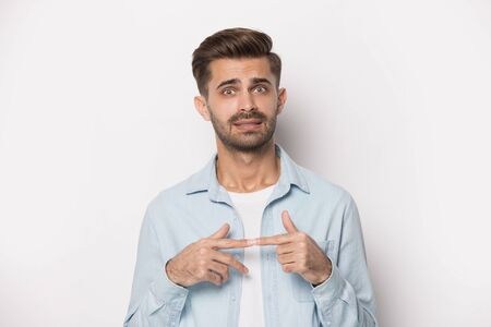 Millennial shocked worried guy feeling uncertain about complicated situation or issue. Stressed nervous young man heard unpleasant fearful news, feeling confused, isolated on white studio background.