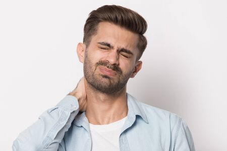 Unhealthy sad exhausted young man suffering from terrible strong neck pain, caused by long sitting on workplace without motion. Unhappy millennial guy massaging neck, has muscular spasm or strain. Banco de Imagens - 138136091