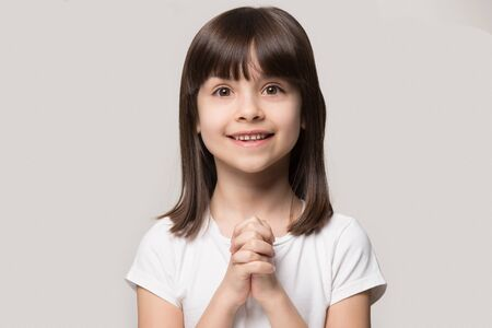 Happy shiny adorable small cute girl folding hands together, asking buy new toy, sweets or need help. Smiling hopeful brown-haired kid child, isolated on grey studio background. May I please concept.