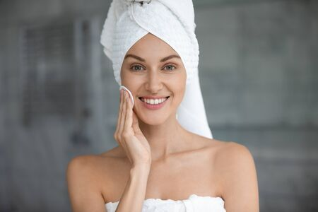 Head shot close up beautiful woman wearing white bath towel on head cleaning skin with cotton pad after shower, pretty female with healthy skin standing in bathroom, looking at camera