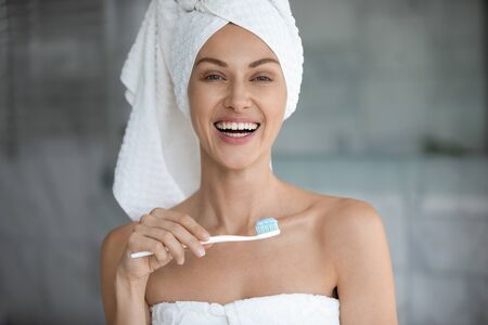 Head shot portrait close up beautiful woman with healthy toothy smile holding toothbrush with toothpaste, pretty young female wearing white bath towel in head looking at camera, morning routine