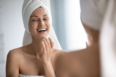 Happy beautiful woman wearing white bath towel on head applying cream on face close up, standing in front of mirror in bathroom, attractive female with perfect healthy skin using moisturizing lotion Banco de Imagens