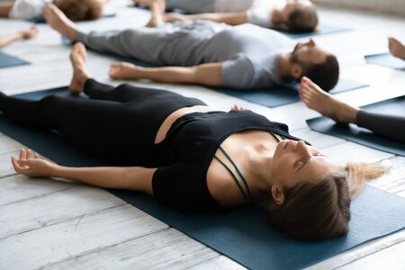 Beautiful young woman meditating in Savasana pose on floor close up, practicing yoga at group lesson, doing Corpse exercise on mats, training, working out in modern yoga studio, center Stock Photo