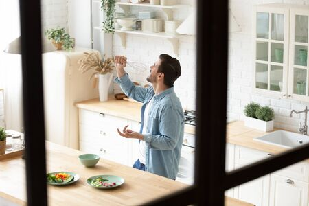 Overjoyed young man having fun at kitchen, imitating microphone with whisk, singing favorite song, pretend to be musician singer, dancing while preparing delicious vegetarian dinner alone at home. Reklamní fotografie - 138134796