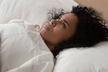 Close up african woman lying in bed having sleep disorder sleeping trouble looking at ceiling cannot fall asleep suffers from insomnia caused by anxiety, stress, depression or noisy neighbours concept Reklamní fotografie