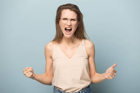 Young beautiful woman in glasses with long hair isolated on blue studio background show strength, strong emotional female model demonstrate girl power and winner gesture, scream with joy Stock Photo