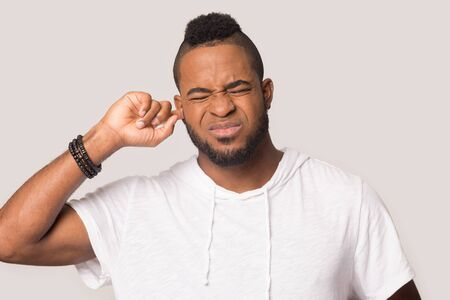 Irritated african American millennial man isolated on grey studio background plug close ear with finger avoid loud noise, annoyed black male feel stressed and bothered hearing noisy sounds Reklamní fotografie