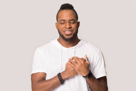Grateful african American man in glasses hold hand close to heart at chest show love and appreciation, thankful black man stand isolated on grey studio background feel pleased and sincere Stock fotó - 138455082