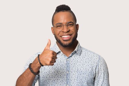 Happy african American male wear glasses isolated on grey studio background look at camera showing thumb up, smiling black young man in spectacles recommend good or service with gesture 版權商用圖片