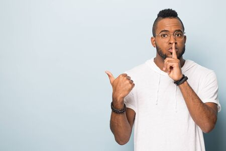Millennial african American man in glasses isolated on blue studio background make hush gesture point at blank copy space aside, black male in casual wear ask do not tell anyone, show good sale offer