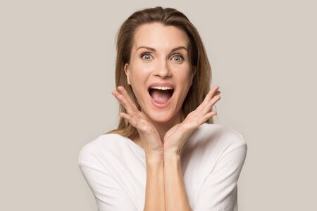 Excited Caucasian millennial woman in casual clothes isolated on grey studio background scream with happiness, smiling happy female shout yell fell euphoric and overjoyed about great sales, discounts Stock Photo